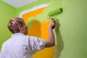 Malerin überstreicht die oragegefärbte Wand mit grüner Farbe
