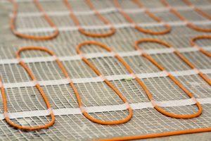 Die Kunststoff-, Kupfer oder Metallverbundrohre einer Wandheizung verschwinden vollständig hinter dem Putz der Mauer © Bilanol_Fotolia.com