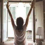 Frau öffnet ein Fenster zum Lüften